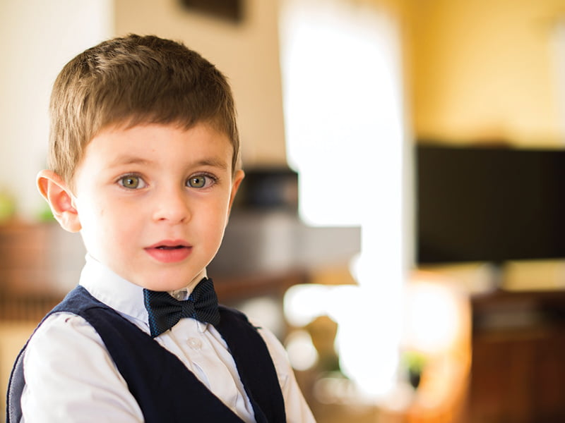 Boy in navy suit and bow tie at wedding