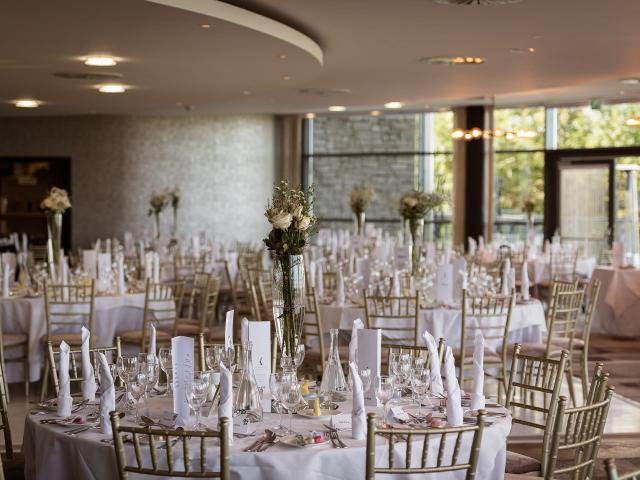 Function room with elegant white design and flowers on the tables